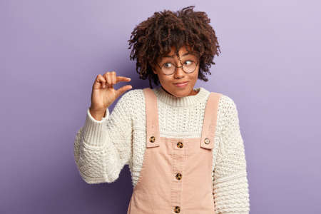 Isolated shot of displeased dark skinned young woman makes small hand gesture, measures tiny object, has confused facial expression, wears white jumper, pink overalls, demonstrates little thing