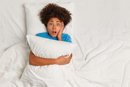 Oh no, I forgot to wake up. View from above of frightened curly Afro American woman embraces pillow, lies in bed on white bedclothes, afraids of dreadful dream, has scared face, stares at camera 免版税图像