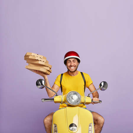Happy piza delivery man busy with his duties, holds pile of carton boxes, drives scooter, wears helmet and yellow t shirt, isolated on purple background, works in pizzeria, represents restaurant well