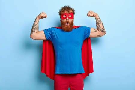 Confident red head male superhero wears mask and red cape, raises arms, shows muscles, represents power and courage, ready to defend people, has shocked expression, isolated on blue background