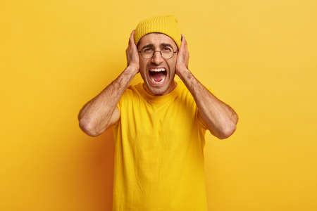 Depressed fed up stressful man looses temper, yells and screams loudly, covers ears, annoyed with loud unpleasant sound, being well dressed, isolated on yellow background, relieves from stress.