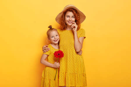 Portrait of lovely woman in straw hat, yellow summer dress embraces her preteen daughter who holds red gerbera, have walk together, take care about each other. Family, relationship, love concept