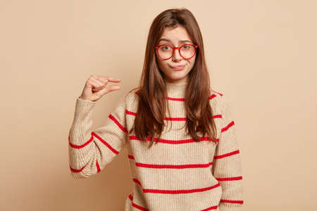Attractive young woman with dissatisfied expression, shows little small gesture, purses lips in displeasure, wears red rim spectacles and striped jumper, isolated over beige background. Too little