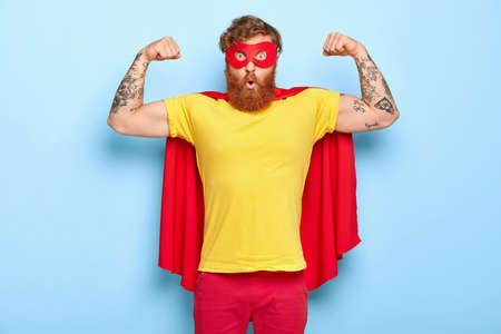 Emotive surprised male hero has noble qualities, demonstrates strength with raised arms, has strong muscles, dressed in superhero costume, isolated on blue, has strength to face dire situation in life