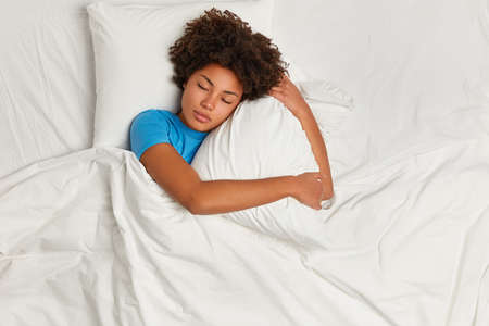 Dark skinned restful woman lying in bed and sleeps peacefully, hugs pillow, enjoys comfort and softness of bedclothes, wears blue t shirt, has healthy sleep at night. Good rest and bed time.