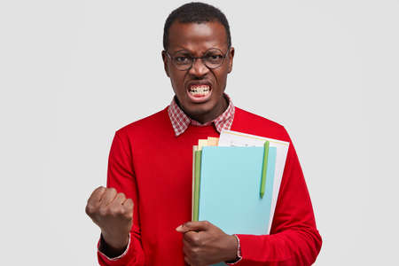 Furious dark skinned man clenches fists, shows white teeth, carries textbooks, feels annoyed with something bad, dressed in red jumper and shirt, isolated over white background. People and anger