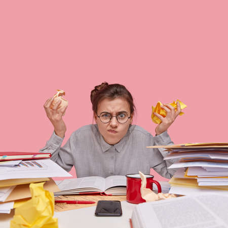 Indoor shot of annoyed young Caucasian woman frowns face, wears spectacles and shirt, holds crampled face, uses mobile phone for communication, has pile of books, isolated over pink background