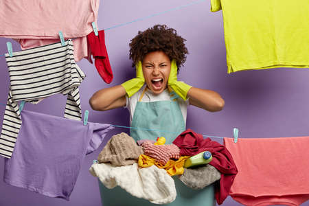 Stressful discontent woman feels overworked, shouts from anger, does laundry alone, demands husband to help, stands near clotheslines with hanged linen, wears gloves and apron. Much housework