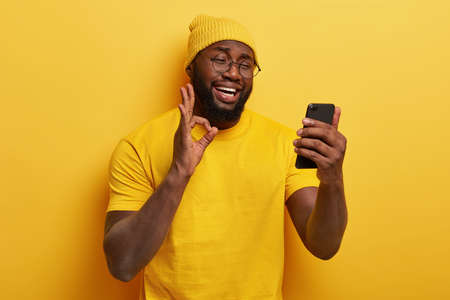 Satisfied dark skinned man makes video call via cell phone, makes okay gesture, confirms everything is fine, wears yellow t shirt, laughs positively, stands against bright background. Technology