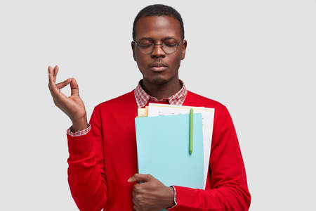 Photo of concentrated young black man meditates indoor, makes ok gesture, carries notepad with pen, wears round spectacles and red sweater, models over white background. Afro American schoolboy