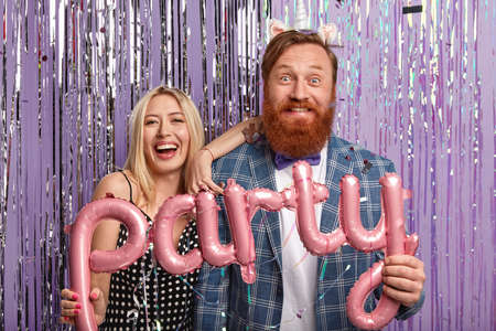 Photo of cheerful young people spend free time at night club, hold balloons in form of letters, wear festive apparel, isolated over purple studio wall. Millennial female and male entertain on party