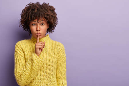 Confident serious female model with dark skin, curly hair, makes silence gesture, whispers secret, gossips with friend, wears yellow knitted sweater, demonstrates hush sign. Body language, conspiracy