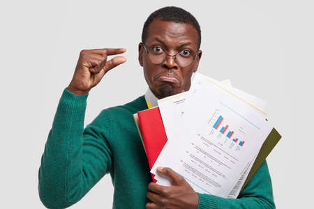 Photo of displeased dark skinned business owner studies information data in documents, demonstrates small gesture, dissatisfied with low company income, isolated over white background. Too tiny