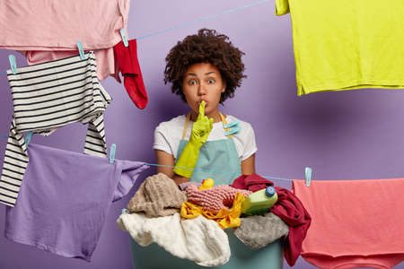 Speechless secret woman makes shush gesture, dressed in domestic clothes, does housework pegs out wet laundry on ropes tells secret of keeping cleanliness at home. Housewife poses among drying clothes