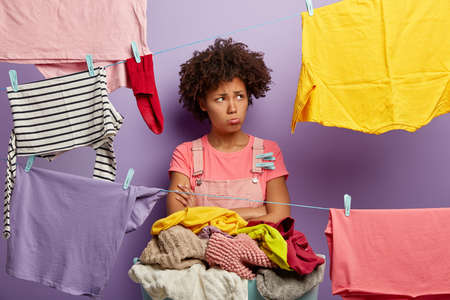 Offended miserable African American woman looks aside, purses lips, crossed hands, doesnt want to do household duties, stands against purple background with clotheslines and laundry. Negative emotions