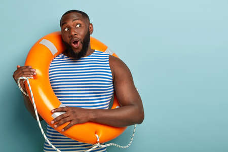 Safe summer holiday concept. Impressed black bearded lifeguard poses with rubber lifebuoy, ready for emergency situation on water, looks surprisingly aside at free space against blue background Фото со стока