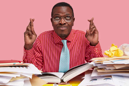 Indoor shot of black male has big hope, crosses fingers for good luck before exam, wears elegant clothes, surrounded with pile of documents, isolated on pink background. Body language concept Standard-Bild