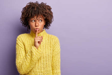 Suspicious beautiful woman asks be queit with finger on lips, looks aside, tells secret information, focused aside, asks keep mouth closed, wears yellow clothes, isolated on purple background Banco de Imagens