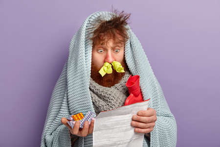 Healthcare concept. Unhealthy stupefied foxy man stares at medical leaflet, surprised with side effect of tablets, warms with coverlet and hot water bag, cures fever and cold, has tissues in nostrils