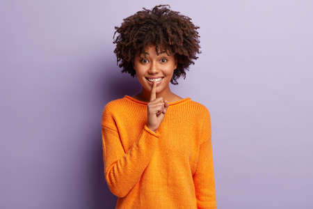 Positive woman with cheerful expression makes hush gesture, asks not spread rumors, dressed in orange clothing, isolated on purple background, orders keep silent. Shut your mouth. Let us make surprise