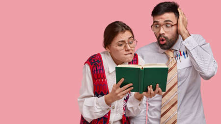 Puzzled worried nerds look nervously at opened green book, find answer on question, wear spectacles and old clothes, pose over pink bckground with blank space on left side for your promotion