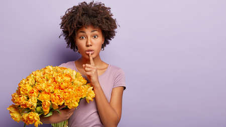 Horizontal shot of secret lovely woman keeps fore finger over lips, tells private information to close person, asks not tell who presented flowers, carries big bunch of yellow tulips isolated on lilac