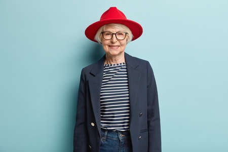 Fashionable grey haired lady with wrinkled face, wears red stylish hat, jacket and jeans, has pleasant smile, feels self assured in her beauty, isolated on blue background, has happy relaxed look
