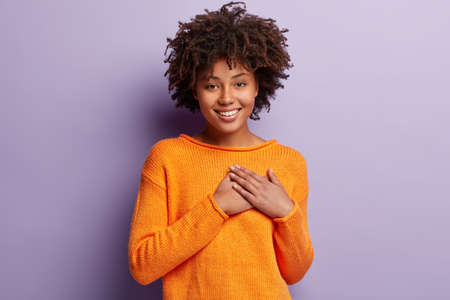 Positive woman with Afro haircut, pleasant smile, touches by heart piercing story, keeps hands on chest, has friendly look, wears orange jumper, isolated over violet background. Appreciation 版權商用圖片