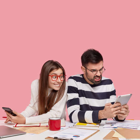 Indoor shot of curious female model peeks at touchpad of classmate, sit shoulder to shoulder at workplace, surrounded with papers, isolated over pink backround with blank space. Youth uses technology