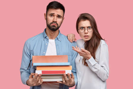 Youth spend leisure time searching information for project wotk in books, enjoy students lifestyle, study together, look with indignation and sad expression, isolated over pink studio background