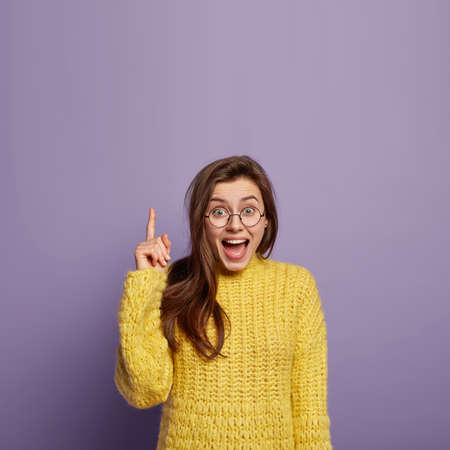 Impressed cute young lady points at interesting surprising object upwards, keeps jaw dropped, wears optical spectacles and yellow jumper, says buy me it in amusement, being curious and excited