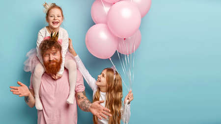 International childrens day concept. Fatigue bearded male entertainer at kids party, amuses girls, gives piggyback, looks clueless as doest know which game to suggest. Small child with balloons