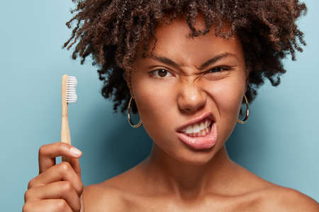 Displeased Afro woman frowns face, clenches teeth, takes care of oral hygiene, has curly hair, holds toothbrush, demonstrates bare shoulders, poses over blue background. Stomatology, whitening