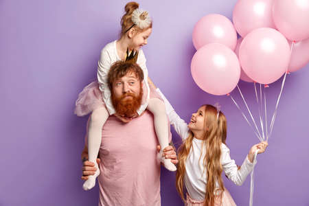 Single father feels tired to bring up naughty disobedient daughters, prepare for family holiday, carry bunch of air balloons, organize party for children, pose together in studio over lilac background