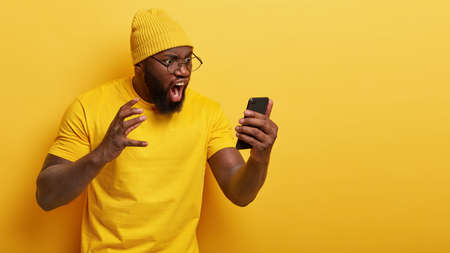 Outraged annoyed dark skinned man stares angrily at smart phone screen, shouts with irritation, dissatisfied with received message, has thick beard, wears casual yellow t shirt and headgear. Standard-Bild