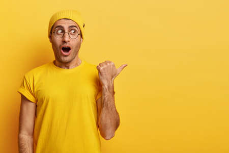 Astonished scared man shocked witnessing incredible thing happend, points thumb on right side, keeps mouth opened with wow sound, holds breath, wears transparent eyewear, casual yellow apparel Stock fotó