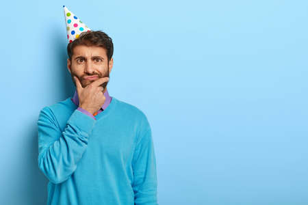 Thoughtful student thinks over graduation party, prepares for celebration, holds chin, looks seriously at camera, dressed in festive clothes, cone hat isolated on blue wall empty space for inscription