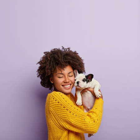 Vertical shot of glad lady stands in purple studio with cute french bulldog puppy, closes eyes from pleasure, happy to get pet from friend on birthday, expresses love, have friendly relationships.