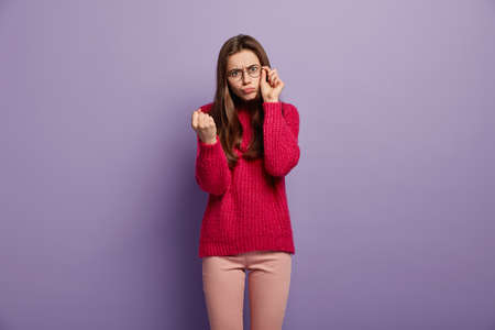 Shot of dissatisfied European woman shows fist with anger and irritation, promises to revenge for bad treatment, keeps hand on frame of spectacles, wears red sweater, models over purple studio wall Stock fotó