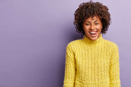 Waist up shot of good looking cheerful dark skinned woman licks lips with tongue as sees something tasty, delicious, being hungry, shows white teeth, wears yellow jumper, models over purple wall