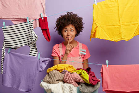 Surprised dark skinned woman makes silence gesture, asks not tell secret, busy with housework, hangs clean wet clothes on washing line, stands against purple wall, uses plastic colorful clothespins Banco de Imagens