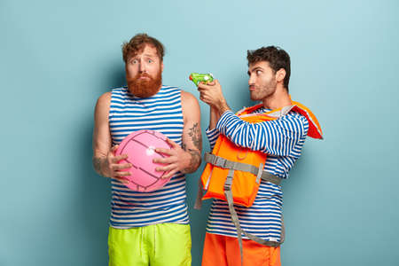 Insecure bearded man with foxy hair, holds ball plays water game with friend. Serious guy wears life vest shoots with squirt gun in guy, has serious expression. Two tourist have fun at beach on summer 版權商用圖片