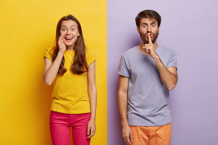 Positive young female whispers secret with glad expression, serious guy keeps fore finger on lips, gossips and spread private information, wear casual t shirts, stands against colorful background