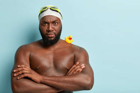 Indoor shot of serious strict swimming coach has muscular arms folded over chest, angry with trainee, helthy dark skin, wears goggles and swimhat, small rubber yellow duckling on strong shoulder