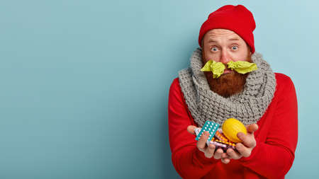 People, disease and medicine concept. Sick unhappy man has running nose, carries medicaments and lemon, wears warm clothes, feels cold, cures illnes in different ways, poses over blue background Stockfoto