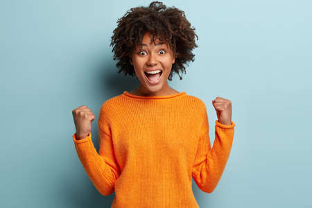 Horizontal shot of attractive woman clenches fists in victory gesture, exclaims with happiness, dressed in orange jumper, triumphs something, isolated over blue background, rejoices from excitement