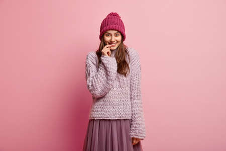 Pretty lady with satisfied expression, keeps hand near lips, hears something positive, wears winter outfit, looks at camera with pleasure and delight, models over rosy background. Emotions concept