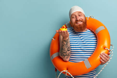 Happy friendly red haired man holds rubber yellow duckling, enjoys swimming in sea during hot summer day, wears swimhat, uses special ring buoy as doesnt have skills, stands against blue wall