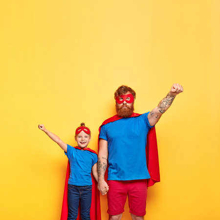 Vertical shot of self confident dad and little daughter clench fists, make flying gesture, hold hands, being team of superheroes, wears special costumes, isolated on yellow background with free space