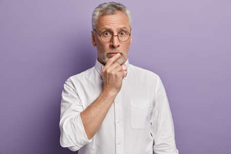 Isolated shot of surprised male keeps hand on mouth, dressed in elegant shirt, poses over purple background, hears something astonishing. Old grey haired pensioner has astonished expression.